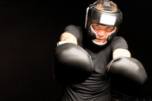 Boxer slaat met beide vuisten in de richting van de camera met een vastberaden blik