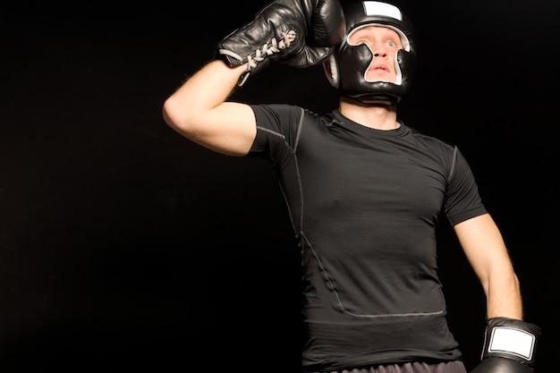 Boxer staat met zijn vuist naar zijn hoofd terwijl hij opkijkt