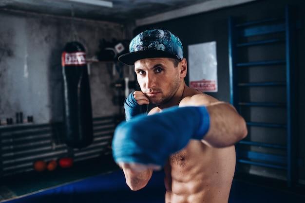 Boxer training in een donkere sportschool. gespierde kickbox of muay thai-jager