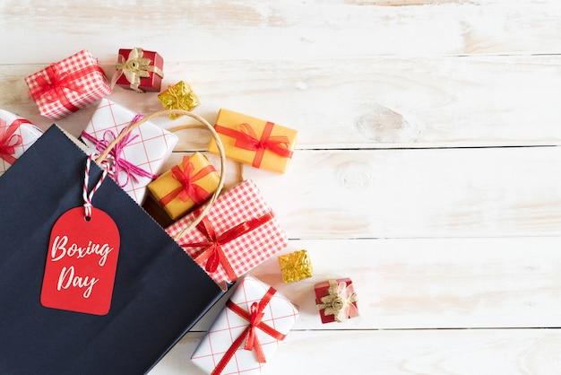 Boxing day verkooptekst op een zwarte tag met boodschappentas en geschenkdoos op een houten witte achtergrond