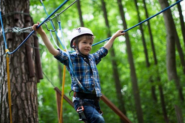 Boy geniet van klimmen in het avontuur van de touwenparcours