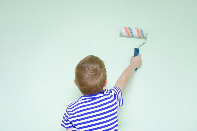 Boy schildert de muurroller om te schilderen. achteraanzicht
