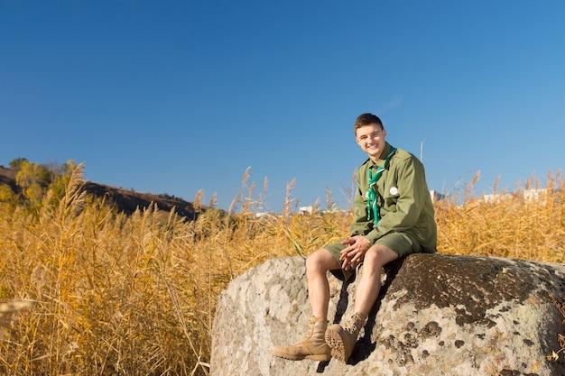 Boy scout rustend op grote rots op het kampterrein terwijl hij naar de camera kijkt, onder een blauwe lucht erboven.
