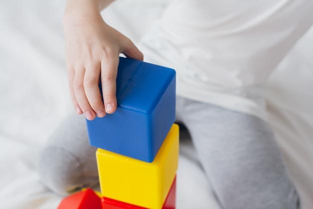 Boy speelt en bouwt een toren van kleurrijke plastic kubussen