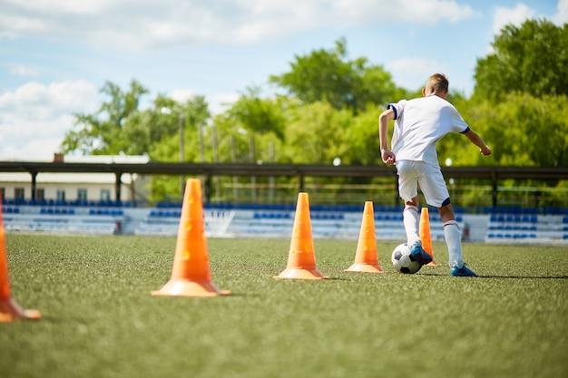 Boy training voor voetbalspel
