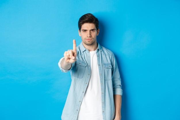 Boze 25-jarige man die vinger schudt in afkeuringsteken, teleurgesteld fronst, iets slechts verbiedt, nee zegt, staande tegen een blauwe achtergrond