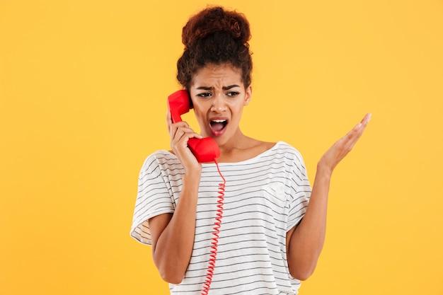 Boze afrikaanse vrouw die terwijl het spreken op rode telefoon gilt
