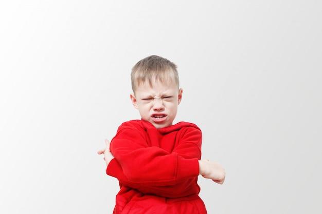Boze agressieve verontwaardigde jongen. kind in een rode hoodie drukt woede uit. opwinding en frons. stress, autisme. verstoor frustratie en onheil