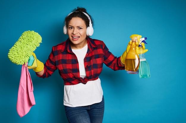 Boze amerikaanse vrouwen schoonmakende producten in handen die de camera verbijsterd bekijken vóór aankomend huiswerk