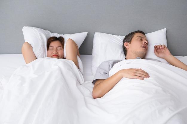 Boze aziatische vrouw geïrriteerd met mannen snurken