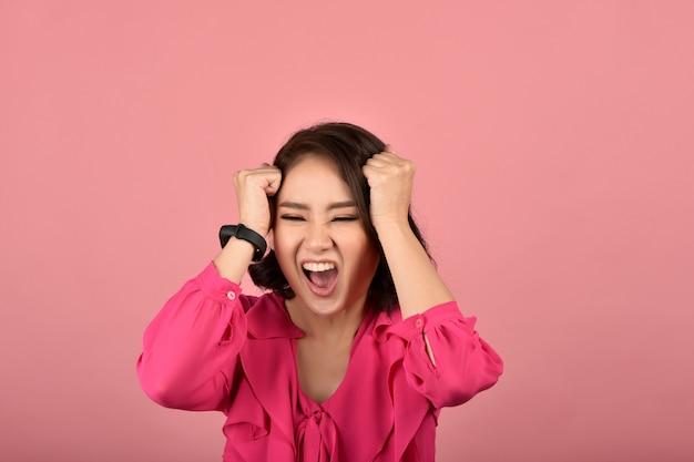 Boze aziatische vrouw, schreeuwende vrouw met woedend agressief handgebaar op roze muur, gezichtsuitdrukking en menselijke emotie.