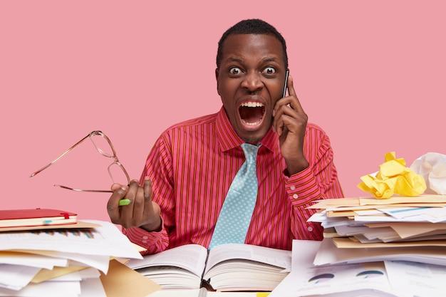 Boze baas concept. woedende man met donkere huid voert telefoongesprek, houdt bril in de hand, schreeuwt van irritatie, gekleed in formele outfit
