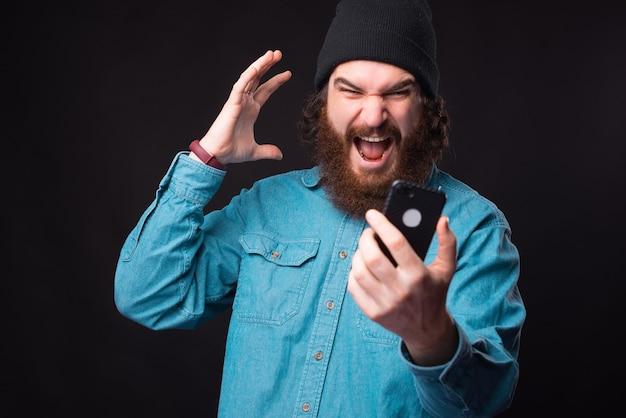 Boze bebaarde hipster man schreeuwen op smartphone en gebaren
