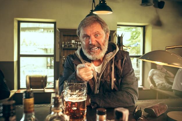 Boze bebaarde man alcohol drinken in de pub en kijken naar een sportprogramma op tv. genieten van mijn favoriete krieltjes en bier. man met mok bier aan tafel zitten. voetbal- of sportfan. menselijke emoties concept