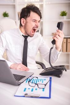 Boze bedrijfsmens die bij telefoon in zijn bureau gilt