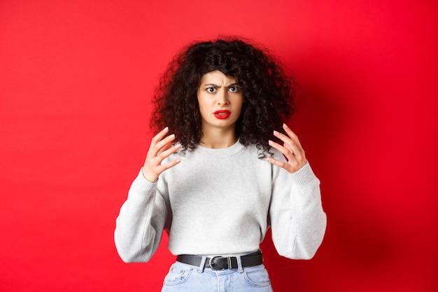 Boze blanke vrouw fronst en steekt handen gek op, wil iemand die irritant is, wurgen of doden, staande op een rode achtergrond