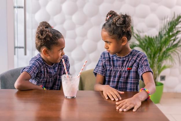 Boze blik. schattige kleine modieuze dochters kijken elkaar boos na ruzie in cafetaria