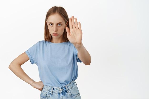 Boze blonde vrouw strekt hand uit en fronst, zegt nee, oneens, weigert of weigert, verbiedt actie, oneens met persoon, staande over witte muur