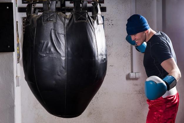Boze bokser met strenge blik in een hoed en bokshandschoenen training met bokszak boksen