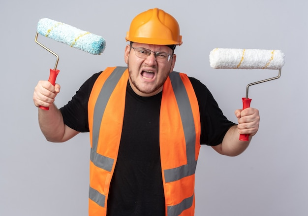 Boze bouwman in bouwvest en veiligheidshelm met verfrollers schreeuwend met agressieve uitdrukking