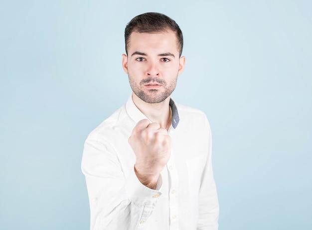 Boze brunette balt zijn hand tot een vuist, kijkt boos naar de camera, dreigt, in een wit overhemd op een blauwe muur