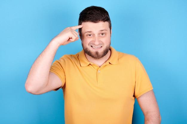 Boze brunette man schreeuwen, woede en gekke uitdrukking. geïsoleerd op blauwe achtergrond.