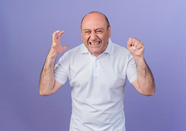 Boze casual rijpe zakenman hand in de lucht houden en papier verpletteren met hand geïsoleerd op paarse achtergrond