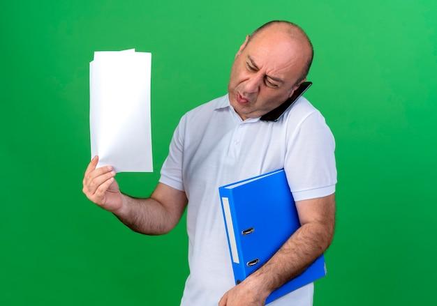 Boze casual volwassen man spreekt over telefoon en map met papier te houden