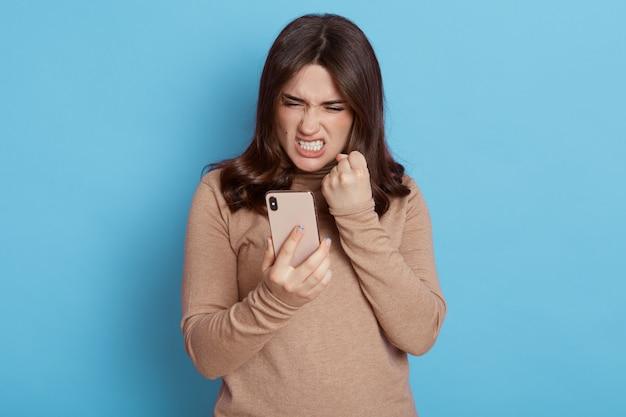 Boze casual vrouw met behulp van slimme telefoon geïsoleerd op blauw