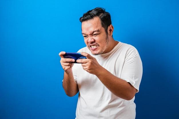 Boze dikke aziatische kerel die games speelt op tablet-smartphone