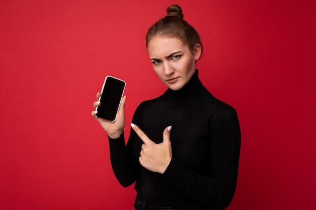 Boze droevige aantrekkelijke positieve jonge donkerbruine vrouw die zwarte sweater draagt die zich geïsoleerd over rood bevindt