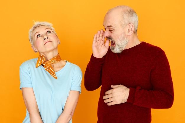Boze emotionele bejaarde man in vrijetijdskleding hand in hand, mond wijd openend en schreeuwend naar zijn onzorgvuldige vrouw die naar boven kijkt, alsof hij hem niet hoort, geen aandacht schenkt