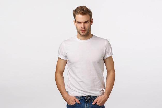 Boze en aantrekkelijke blonde bebaarde man in wit t-shirt