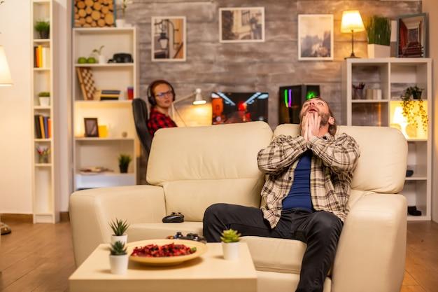 Boze en gefrustreerde man videogamespeler op de bank 's avonds laat in de woonkamer