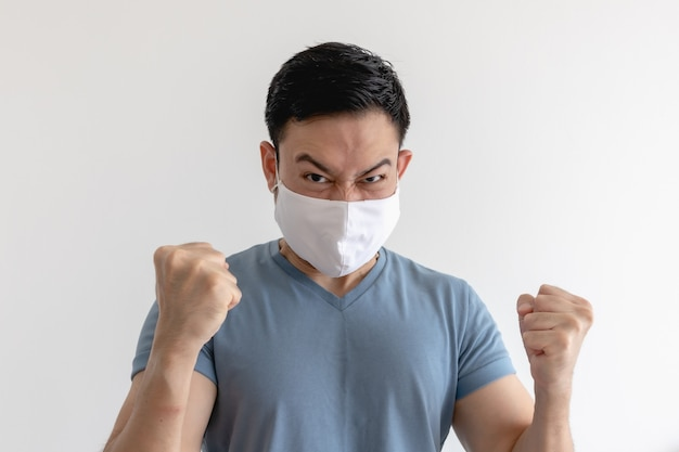 Boze en gekke aziatische man in gezichtsmasker op geïsoleerde witte ruimte.