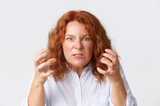 Boze en hatelijke roodharige vrouw van middelbare leeftijd die verontwaardigd en gekweld kijkt