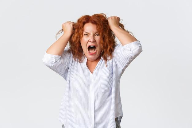 Boze en hatelijke roodharige vrouw van middelbare leeftijd die woedend en gekweld kijkt