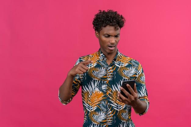 Boze en nerveuze donkere man in bladeren bedrukt hemd die naar mobiele telefoon kijkt en met wijsvinger wijst