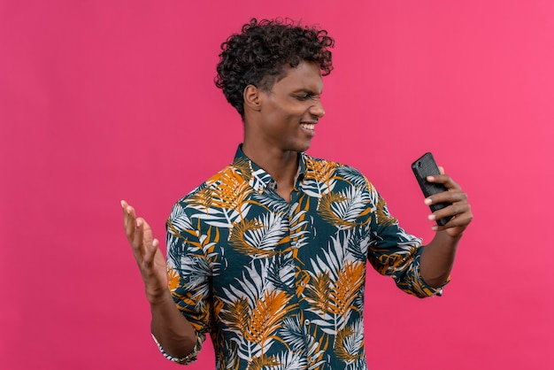 Boze en nerveuze donkere man in bladeren bedrukt overhemd kijken naar mobiele telefoon en hand opsteken
