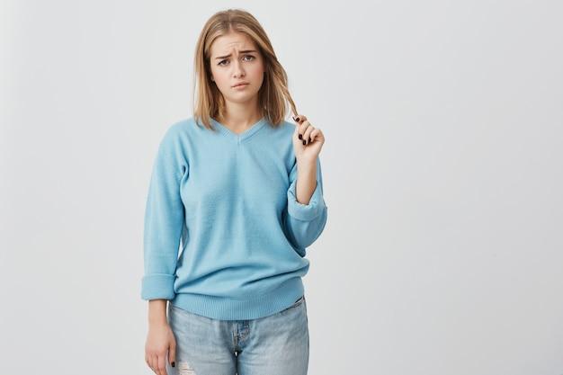 Boze en ontevreden jonge vrouw met een ovaal gezicht, donkere ogen en blond steil haar, gekleed in een blauwe casual trui, fronst haar wenkbrauwen en speelt met haar haar, ontevreden over iets.