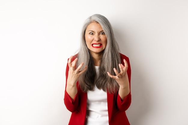 Boze en pissige aziatische senior vrouw gebalde vuisten, grimassen en staren woedend, uiten haat en ergernis, staande tegen een witte achtergrond.