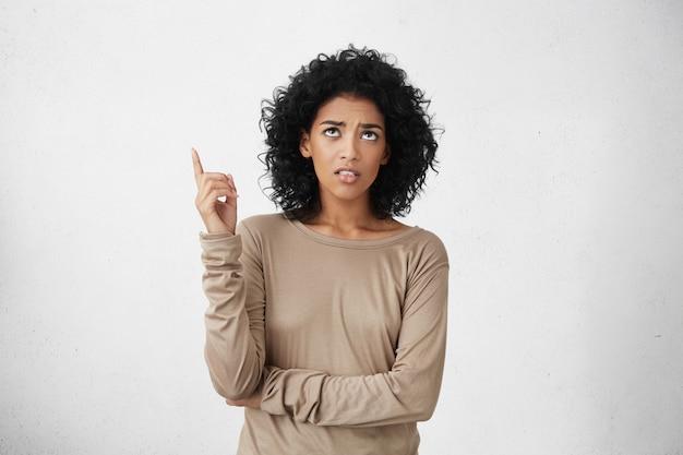 Boze en verontwaardigde jonge vrouw van gemengd ras met afro-kapsel dat opkijkt en wijsvinger naar boven wijst, gek van het geluid van de buren erboven. lichaamstaal