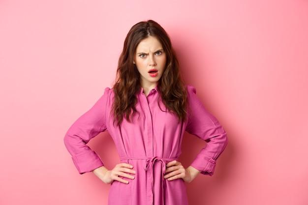 Boze en verwarde vriendin starend van teleurstelling, kijk van onder voorhoofd, fronsend en hand in hand op taille, iemand beoordelen, gedrag veroordelen, tegen roze muur staan.