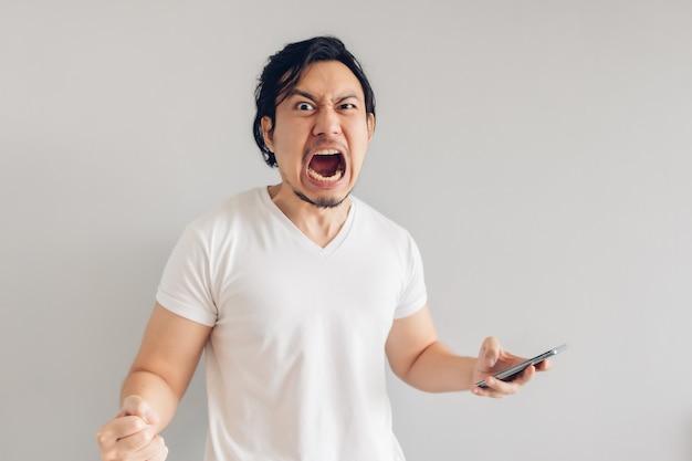 Boze en woedende man met lange haren in wit t-shirt gebruikt smartphone.