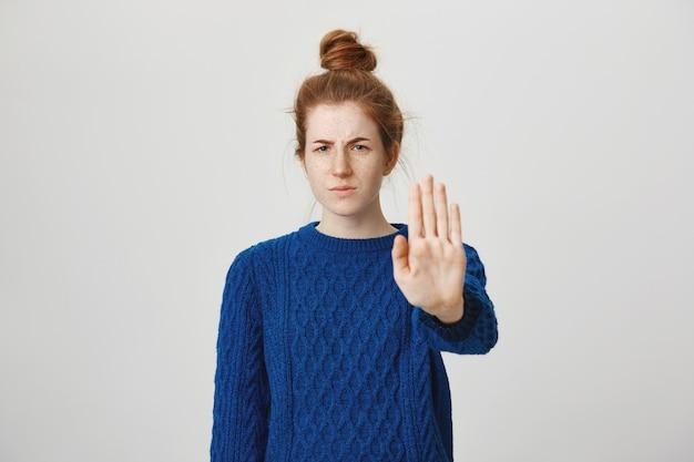 Boze ernstige roodharige vrouw strekt haar hand uit om te laten zien dat ze stoppen, beperken of verbieden