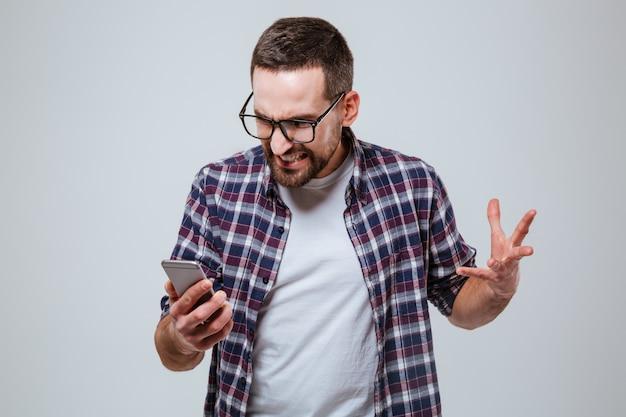 Boze gebaarde mens die in oogglazen telefoon bekijkt