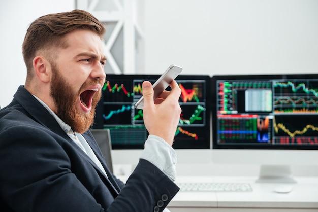 Boze, geïrriteerde, bebaarde jonge zakenman die schreeuwt in smartphone op kantoor