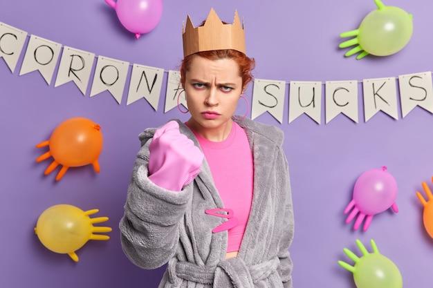 Boze geïrriteerde europese vrouw steekt gebalde vuist op belooft wraak te nemen draagt huiselijke kleding en rubberen handschoen geïrriteerd door coronavirus quarantaineposities boven versierde muur