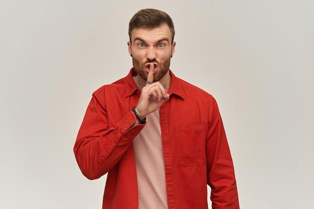 Boze geïrriteerde jonge bebaarde man in rood shirt staan en stilte teken tonen over witte muur kijkend naar de voorkant