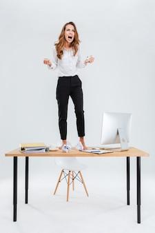 Boze gekke jonge zakenvrouw die op tafel staat en schreeuwt op een witte achtergrond